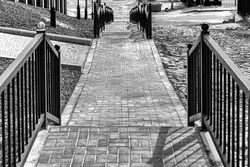Staircase covered with paving stone leading down. Black and white.