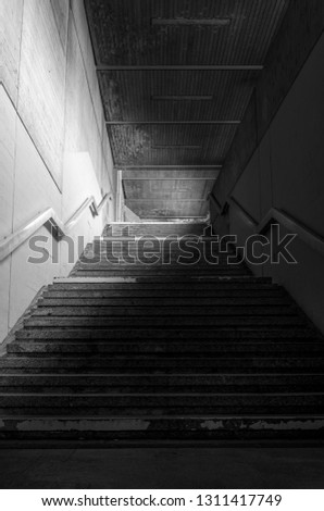 Staircase from an underground passage with concrete walls and metal railing in a low light #1311417749