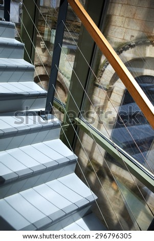 Staircase in a modern building facing an old church