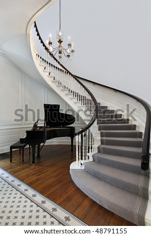 Staircase in front entry with cove for piano