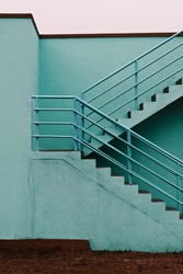 Staircase of a building painted teal. Orange and teal color palette. Abstract lines and patterns in architecture