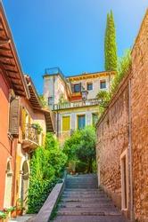 Staircase stairway of narrow street between stone walls. Scalinata Castel S. Pietro leading to Castel San Pietro in Verona city historical centre, blue sky background, Veneto Region, Northern Italy
