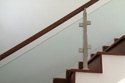 Staircase with glass railing in front of the white wall