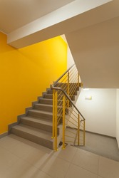 Staircase with yellow walls and metal banister