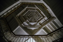 Stairs abstract, bottom view, endless dark spiral staircase