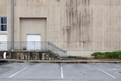 stairs and handrail to entrance to concrete building with mold and parking lot