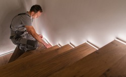 Stairs and Railing Contractor Finishing Wooden Residential Stairs with LED Lighting Illumination. Home Improvement Theme.