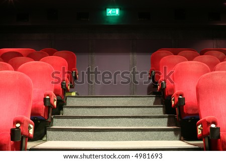 stairs, chairs and an green exit table in a  cinema