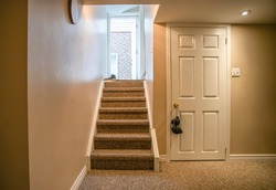 Stairs going out of the basement. Basement door, walkout stairs and at walkout door there are shoes lying around. Picture has basement door, light up on ceiling, light switch.