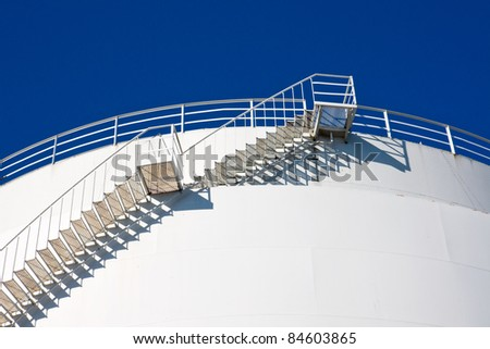 Stairs leading to the sky on a white industrial tank