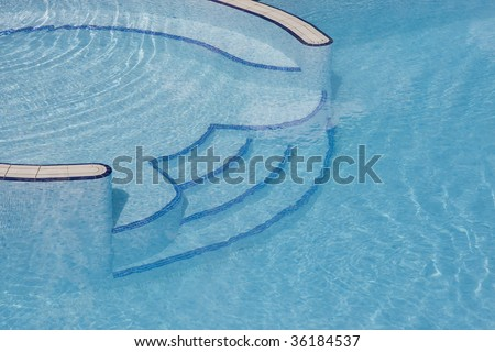 Stairs of a swimming pool with blue water