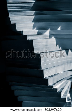 stairs of stacked books in black and white blue toned closeup #603297620