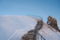 Stairs on a snow-covered hill. Stone ruins of an ancient medieval Rezekne castle in Latgale, Latvia. Blue sky.