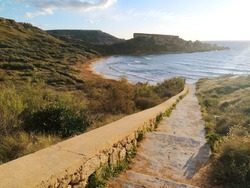 Stairs path to Ghajn Tuffieha (Riviera) Beach in  Mġarr, Island of Malta in the Mediterranean Sea, South Europe. Beautiful sandy beach - ideal destination for a summer vacation. Travel tourism image.