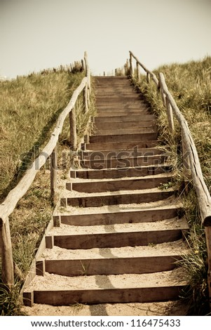 Stairs to the top of a dune. Netherlands. Toned and vignetted image