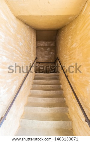 Stairs upstairs in a narrow stone dark passage.