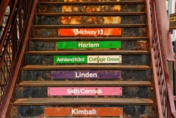 Stairs with colorful signs indicating different lines of Chicago's elevated