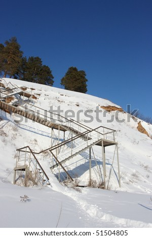Stairs with landing against a snow slope against pines and a blue sky