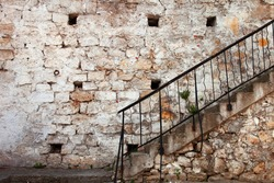 Stairs with railing against the old stone walls. Can be used as background