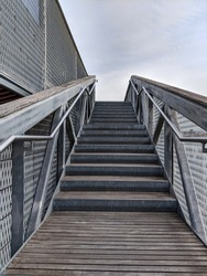 Stairs with stainless steel hand railings and wooden steps. Staircase with the sky in the background. Stairs with steps up.