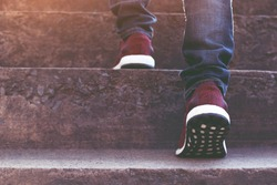 stairway. Close up legs jeans and shoes sneakers red of young hipster man One person walking stepping going up the stairs in modern city, go up staircase, success, grow up. Sunshine in the morning.