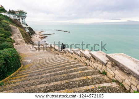 Stairway Passetto Ancona Marche Italy with man sitting on the stairway thinking and watching the sea. The Passetto is a panoramic point over the Adriatic Sea, with concrete stairway symbol of the city