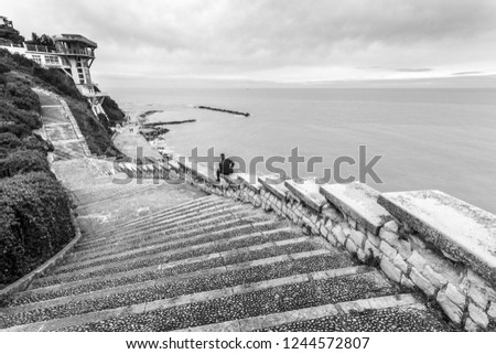 Stairway Passetto Ancona Marche Italy with man sitting on the stairway thinking and watching the sea. The Passetto is a panoramic point over the Adriatic Sea. Black and white.