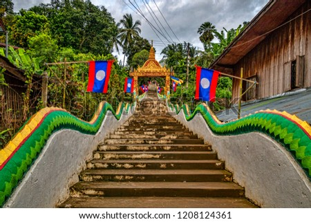 Stairway up Religious Buddhist Hilltop with Laotian Flags, and historic Wooden Buildings (Huay Xai, Bokeo, Laos). #1208124361