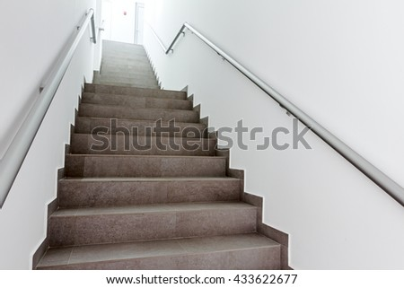 Stairway with metallic banister in a new modern building. Every building is required to have emergency stairways as safety measure. #433622677