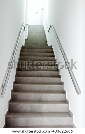 Stairway with metallic banister in a new modern building. Every building is required to have emergency stairways as safety measure. #433622686