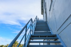 Stairwell fire or emergency exit on wall of building with blue sky background