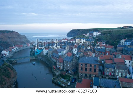 Staithes from high vantage point with fading evening light and smoke from the houses.