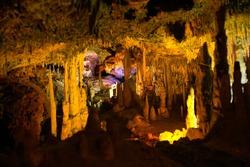 Stalactite illuminated caves in Spain on the island of Mallorca. Multi-colored illumination of caves. Beautiful cave. Stalactites in old cave. Red, green, blue, purple, yellow color.