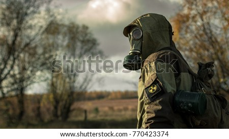Stalker soldier in gas mask and russian military hoodie jacket looking backwards while walking in the danger radioactive zone. Post apocalypse. Nuclear war.