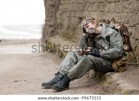 Stalker soldier with chemical armor and the flame gun sitting on the curb and hold the head - stock photo