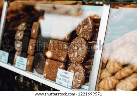 Stall at Nuremberg Christmas market (Christkindlesmarkt) selling baked goods with signs saying 'finest gingerbread cookies' (Nürnberger Elisen-Lebkuchen) and price tags