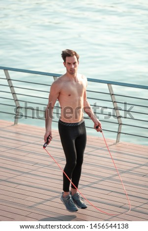 Stamina exercises, young athletic man skipping or jumping rope, working out on his cardio and endurance skills