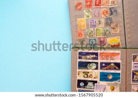 Stamp collecting. Two albums with old expensive valuable post stamps on blue background. #1567905520
