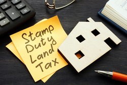 Stamp duty land tax SDLT memo and model of home.