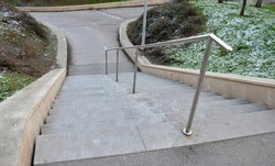 stand in the park made of concrete with a handle made of shiny, stainless steel metal pipes. lower railing is a protection against falling from too long and steep stairs down, it is centrally located