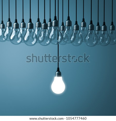 Stand out from the crowd and different creative idea concepts , One hanging light bulb glowing with unlit incandescent bulbs on dark cyan background , 3D rendering.