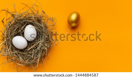 Stand out from the crowd. One unique golden egg standing out of two white eggs in nest, orange background with free space