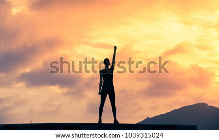 Stand strong. Woman with fist in the air. Feeling motivated, strength and courage concept.