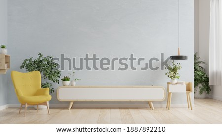 Stand TV in modern living room,Interior of a bright living room with armchair on empty blue wall background.3D rendering