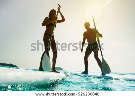 Stand up paddle board couple paddleboarding . Young caucasian couple on summer vacation.