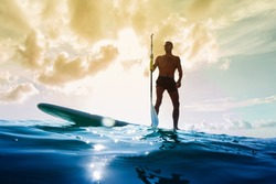 Stand up paddle board man paddleboarding at sunset. Young caucasian male model on summer holidays vacation travel.