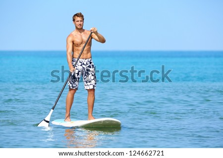 Stand up paddle board man paddleboarding on Hawaii standing happy on paddleboard on blue water. Young caucasian male model on Hawaiian beach on summer holidays vacation travel.