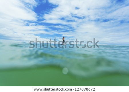 Stand up paddle boarder on open ocean