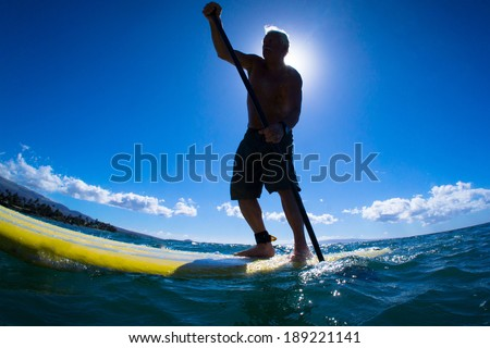 Stand up paddle boarder paddling off the coast of Maui, Hawaii