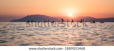 Stand up paddle boarders SUP silhouettes on the water of the sea. Evening, sunset at sea. Active rest on the sea Stock photo ©